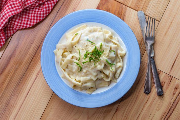 Authentic Italian fettuccine alfredo pasta dish on wooden kitchen table