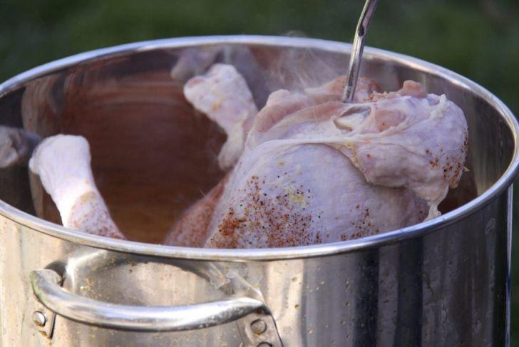 Fried Turkey Inserting Turkey Into Fryer