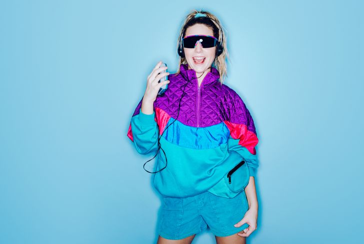 A woman wearing clothing styled after the 1980's and 1990's listens to music