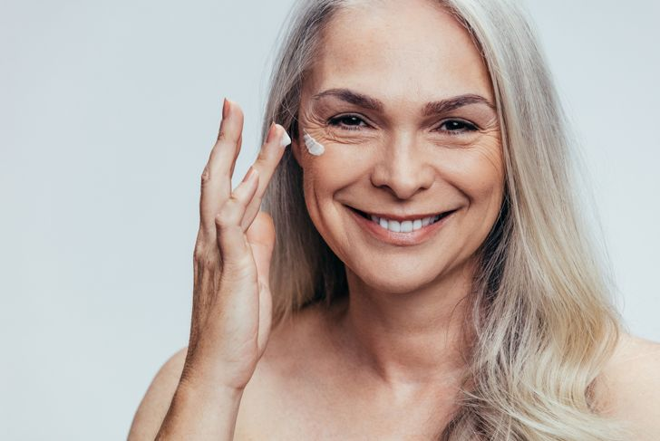 Smiling mid adult caucasian woman applying anti aging cream on her face.