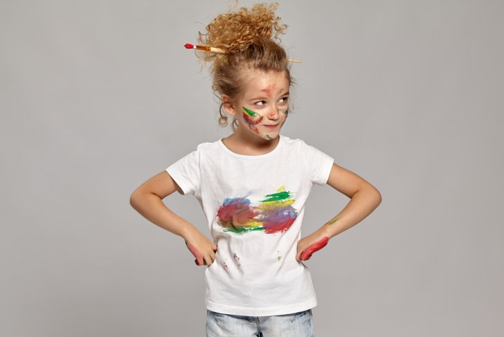 Cute girl having a brush in her lovely haircut, wearing in a white smeared t-shirt.