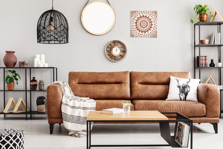 Warm ethno living room with big comfortable leather couch and metal furniture, real photo