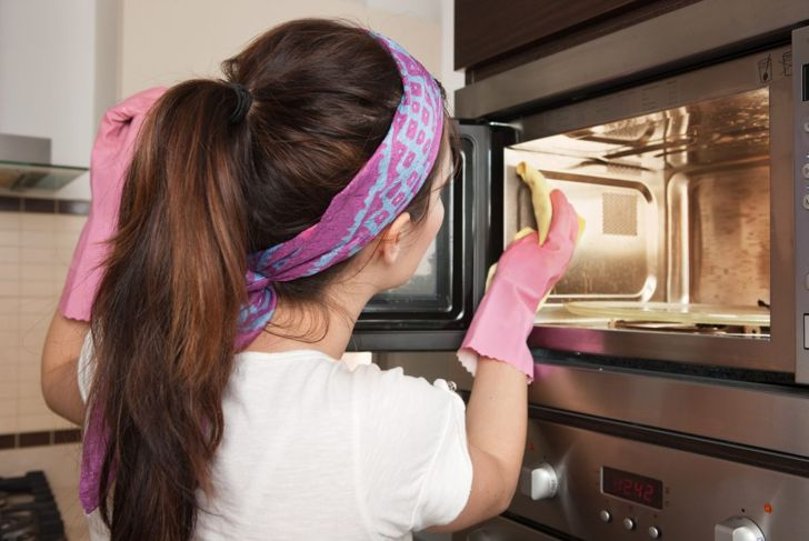Woman Cleaning a Microwave