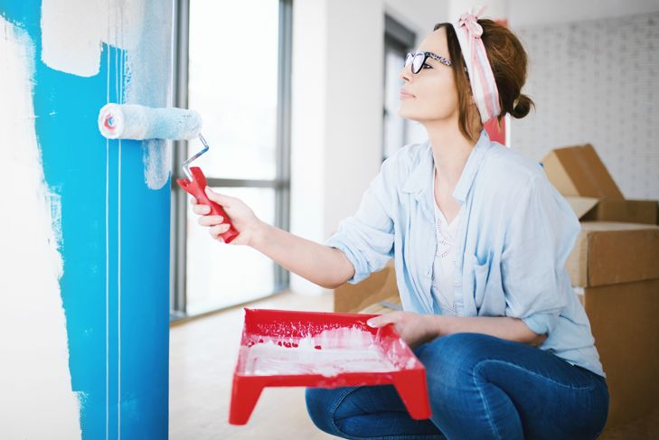 Young woman painting wall, enjoying her home renovation.