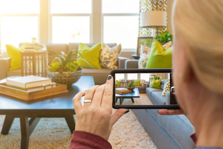 Woman Taking Pictures of A Living Room in Model Home with Her Smart Phone.