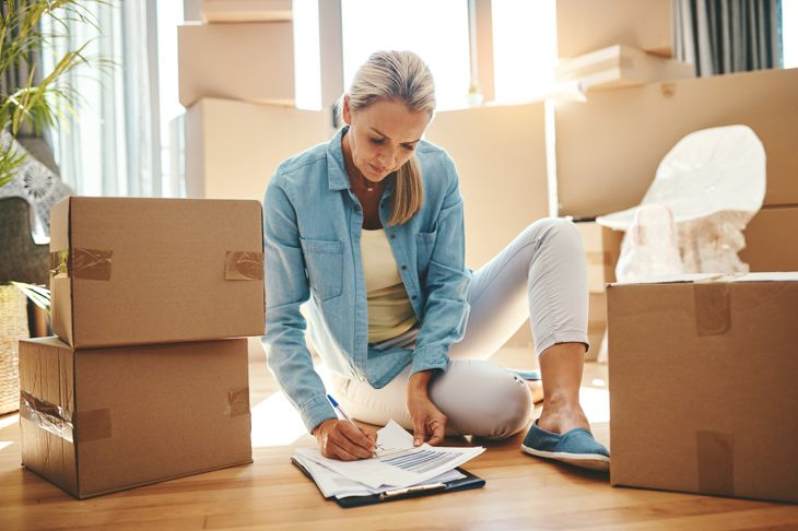 Shot of a mature woman going through paperwork on moving day