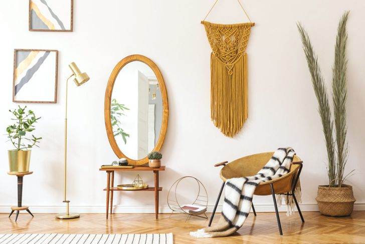 A deep golden-colored macramé wall hanging in an open, airy room