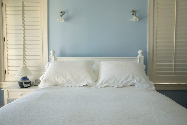 Bedroom with blue walls and white bed.