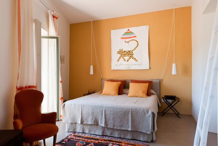 Bedroom with orange wall and orange pillows