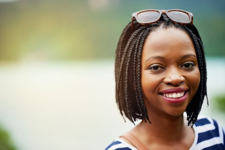 A smiling woman with chin-length box braids