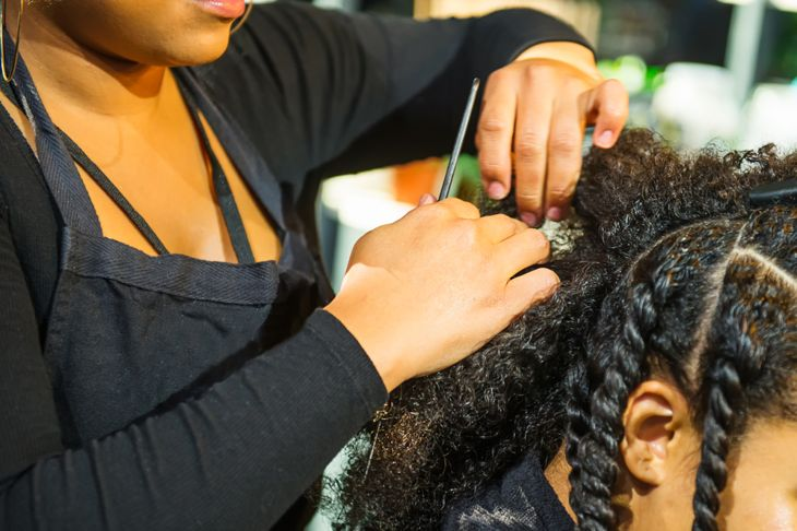 Close up african hairstylist braided hair of afro american female client in the barber salon.