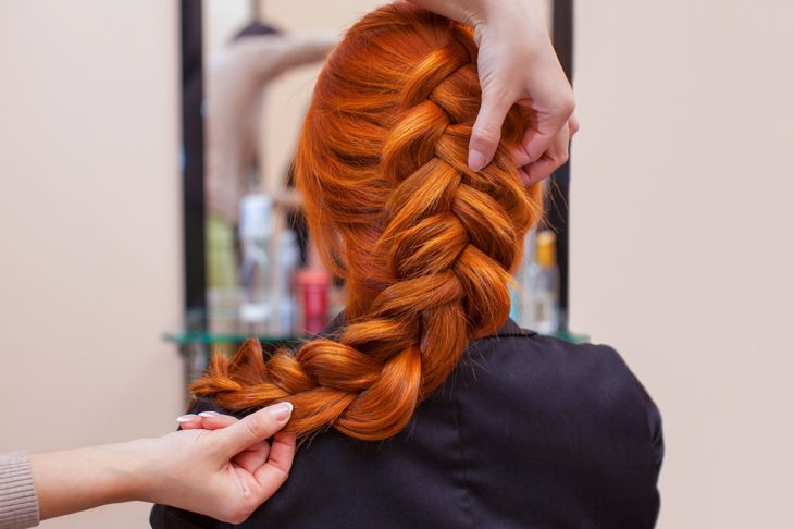 Beautiful, red-haired girl with long hair, hairdresser weaves a French braid, in a beauty salon