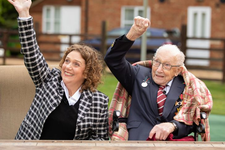 In this handout image provided by Capture the Light Photography, Colonel Tom Moore and his daughter Hannah celebrate his 100th birthday, with an RAF flypast provided by a Spitfire and a Hurricane over his home on April 30, 2020 in Marston Moretaine, England. Colonel Moore, formerly a Captain, received a promotion in honour of his 100th birthday and in recognition of the funds, in excess of £29m, he raised for the NHS by walking laps of his garden.