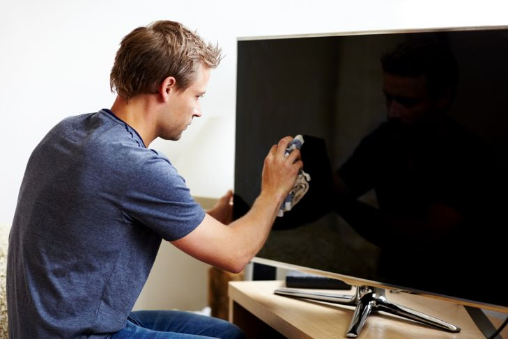 Young man cleaning the screen of his smart TV