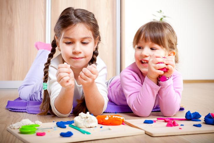Two little girls are playing with plasticine.