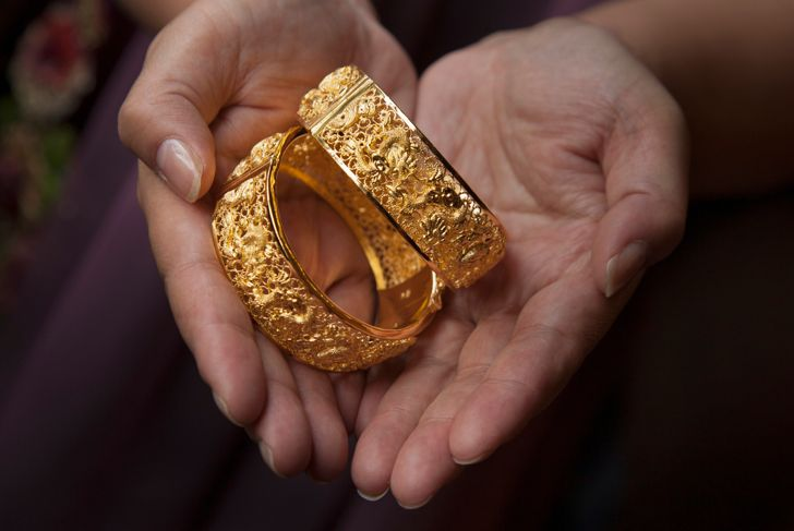 Solid gold bracelets are given as traditional wedding gifts to a Chinese couple. Chinese brides often change dresses during the wedding day mixing traditional Chinese dresses with Western gowns.