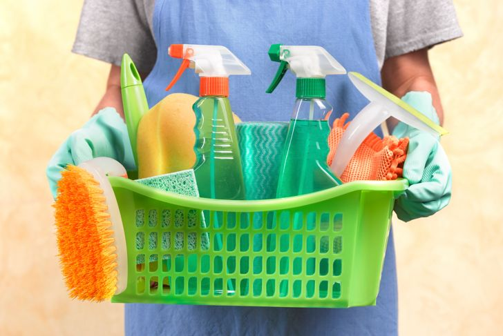 Close up of a woman holding a basket containing cleaning materials.