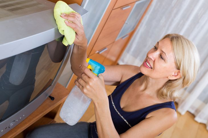 mature woman cleaning TV with rag at home