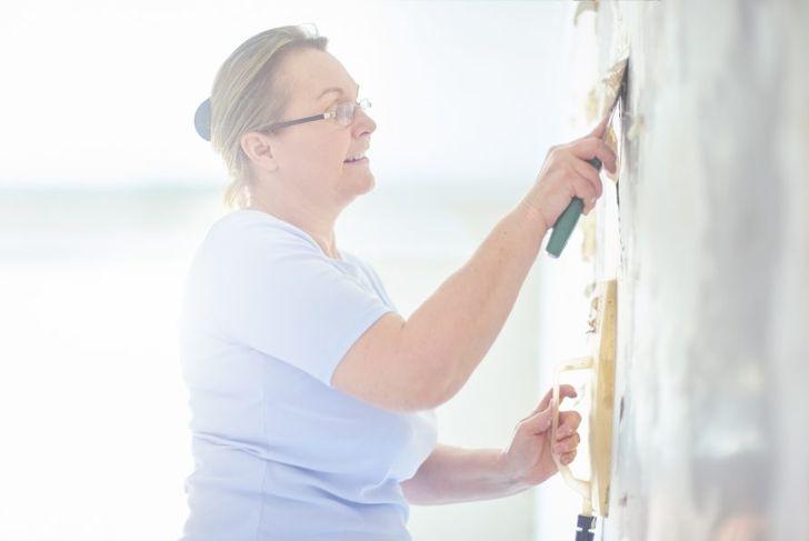 Woman scraping off wallpaper