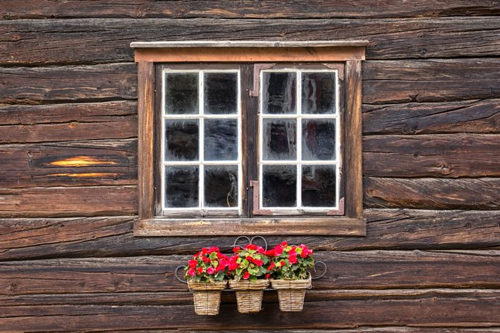 View on a very nice window of a wooden house with begonias in front of the window
