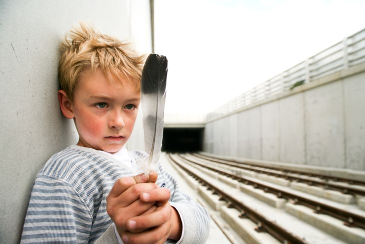 Young boy staring at feather standing beside Rail tracks.