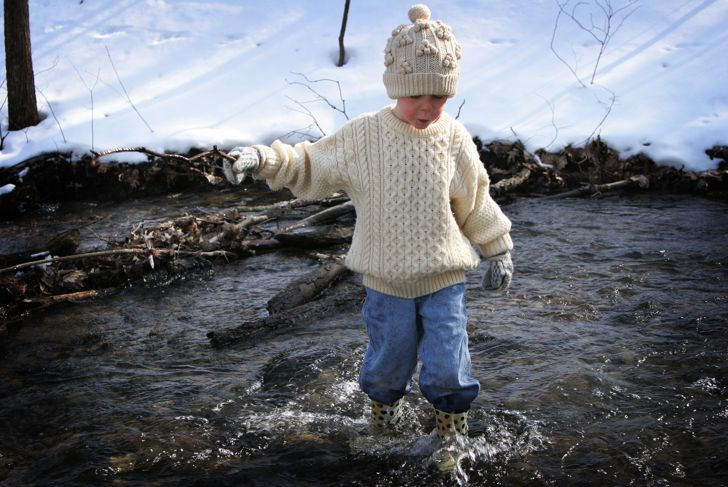 """Little boy enjoys outside, wears wool Irish hat and sweater.  Wades in water holding a stick- classic childhood image.  Some copy space.Shot with Canon 20D, ISO 100"""