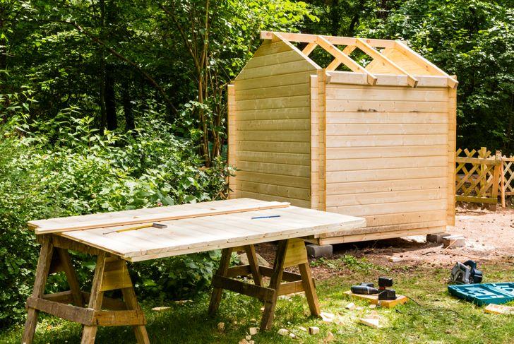 Construction of a wooden hut in a garden