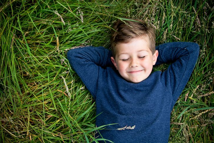 Portrait of a smiling boy lying down on the grass