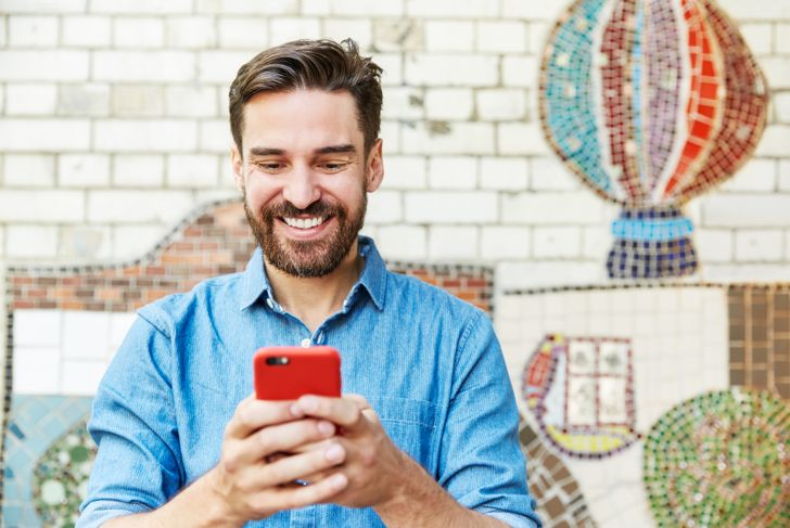 Man with smartphone next to tiled mosaic wall.