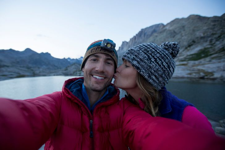 A woman kissing a man while they take a selfie.