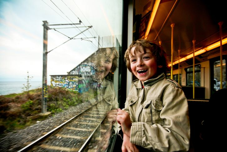 A very excited young boy looks out of a train window.
