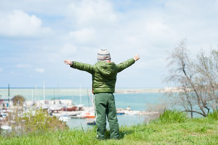 one little boy in jacket and hat stands on green hill on background of sea Bay with ships in early spring