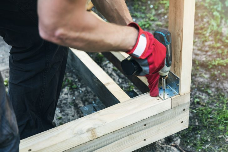 wood shed construction - man screwing corner joint brace