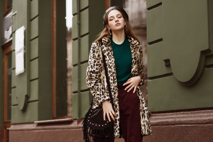 Outdoor fashion portrait of woman wearing trendy animal, leopard print faux fur coat, beret, sweater, corduroy trousers, carrying suede bag with fringe, posing in street of city.