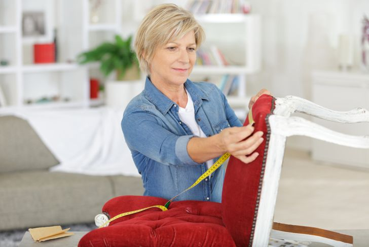 woman measuring chair she is renovating