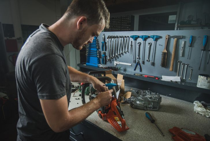 Professional serviceman is repairing a chainsaw using a spanner to untighten screw. Man fixing a chainsaw in a fancy workshop