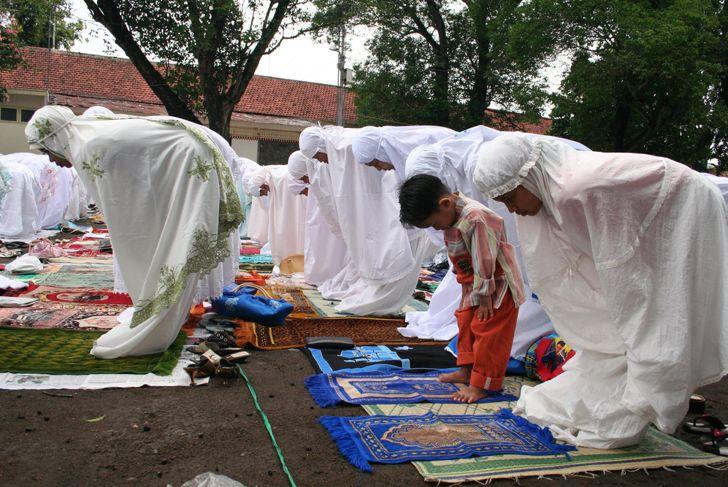 a boy is following Eid al-Adha prayer in the field.