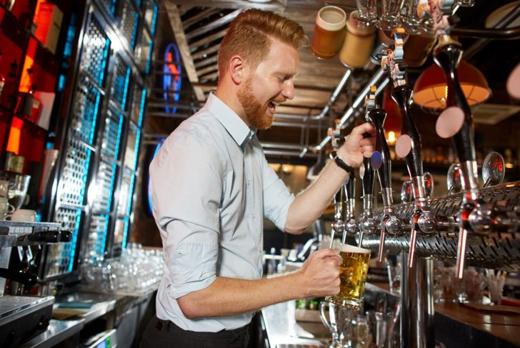 Happy bartender pouring beer