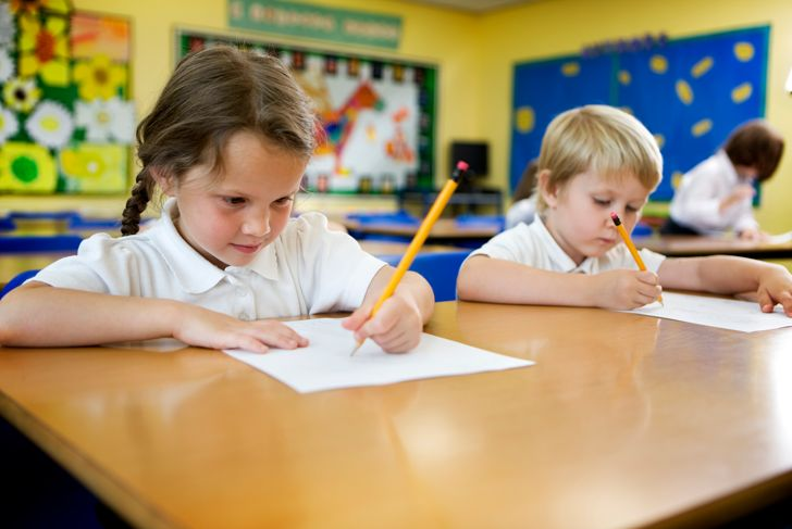 A pair of cute 5 year-old primary school children working hard on their studies in the classroom.