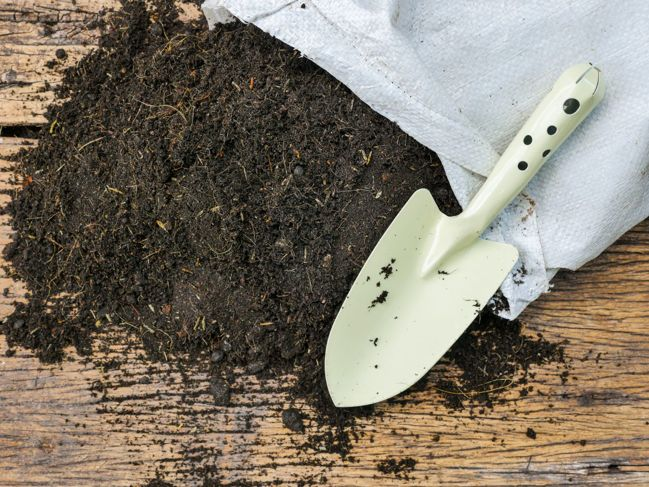 An open bag of potting soil spilled onto a surface with a metal shovel.