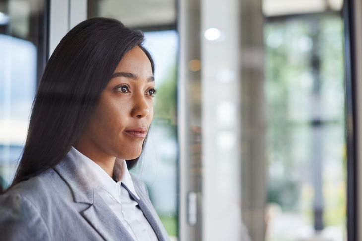 Shot of an ambitious young businesswoman looking thoughtfully out of a window