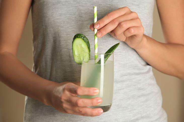 Woman holding glass of fresh aloe vera juice, closeup