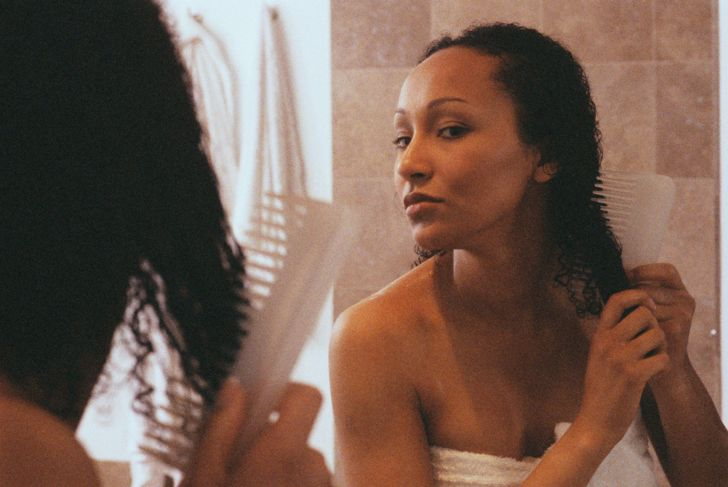 Woman in Bathroom Combing Hair