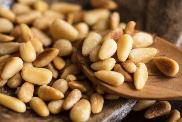 Pine Nuts on Dark Wooden Table. Toasted Organic Healthy Food.
