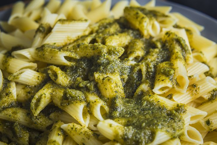 Italian penne pasta close up with green pesto sauce on a tasty food close up still