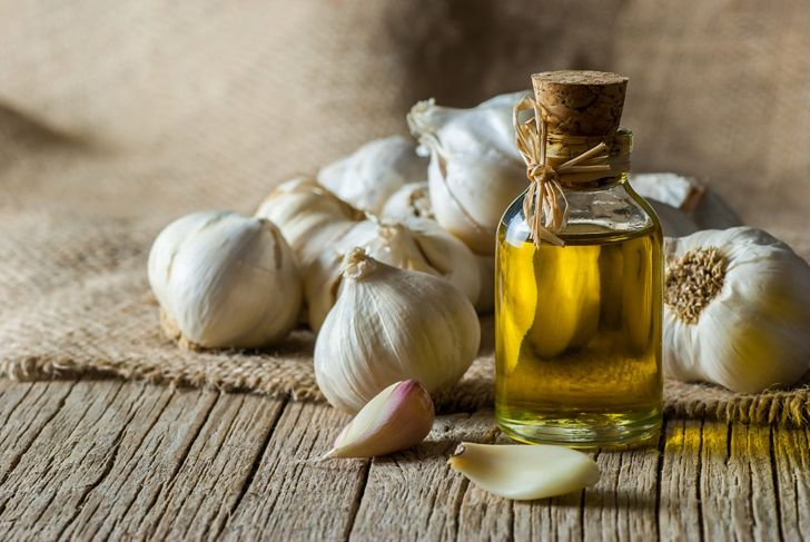 Heads of garlic surround a bottle of snake repellent garlic oil.