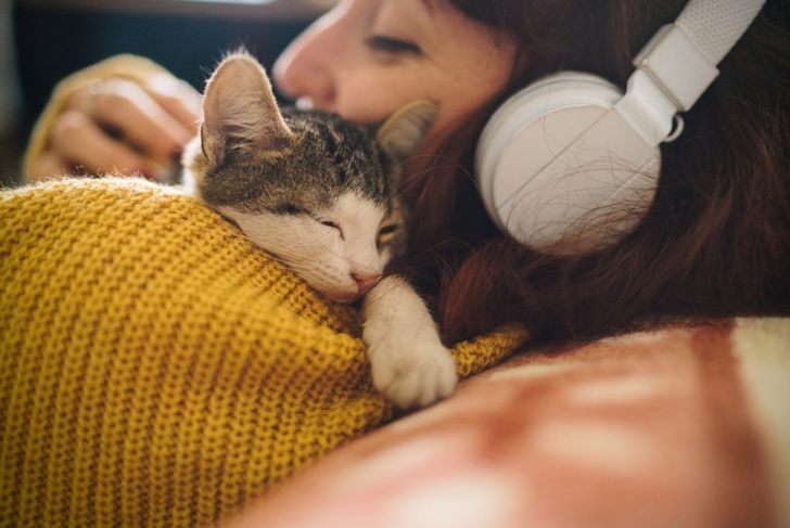 A cat snuggling with a woman on a couch in headphones.