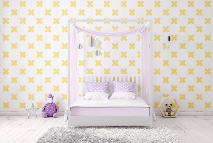 Bedroom with patterned accent wall and polka dot pillows