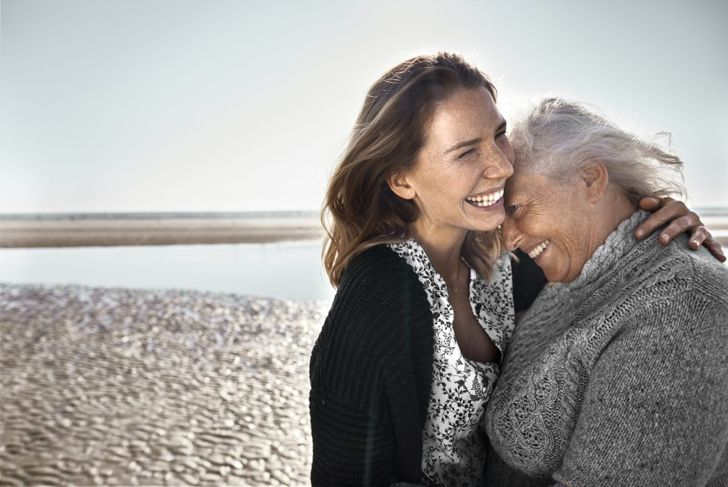 Two adult women embracing on beach