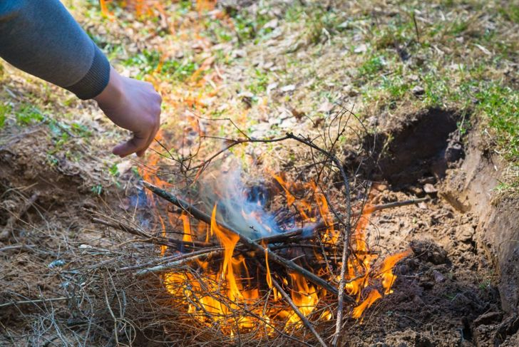 Person prepares a fire pit to use the smoke as a snake repellent.
